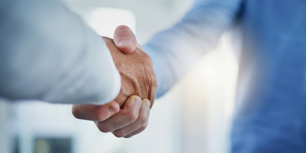 Closeup shot of a two unrecognizable businessmen shaking hands in an office